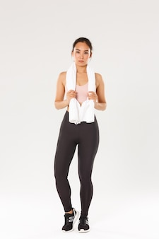Sport, gym and healthy body concept. full length focused and determined young slim girl athlete, sportswoman with towel standing after productive workout, sweat from fitness exercises.