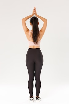 Sport, gym and healthy body concept. full length rear view of slim brunette asian girl in active wear practice yoga, workout alone, standing with hands clasped over head in asana, meditating.
