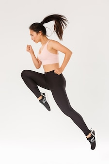 Sport, gym and healthy body concept. full length of serious focused female runner, motion shot of girl running in air, fitness training of cute slim sportswoman, athlete workout in active wear.