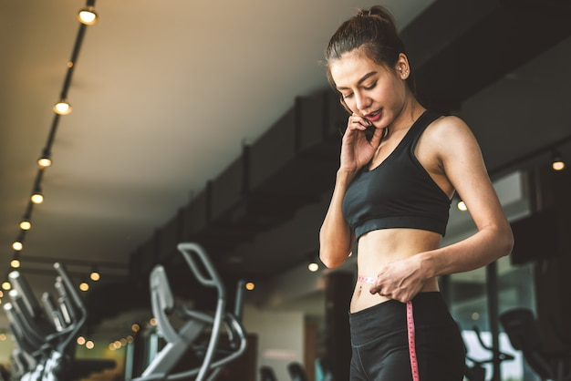 Sport happy slim woman using waist tape line in fitness gym sport club training center