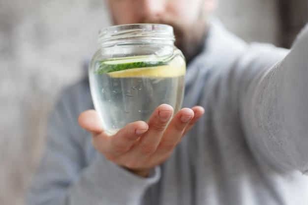 スポーツ、健康、人、感情、4k、ライフスタイルのコンセプト-スローモーションで水を飲むフード付きの男性のハンドヘルドショット。ガラスにレモンとキュウリのスライスを入れた新鮮な飲み物