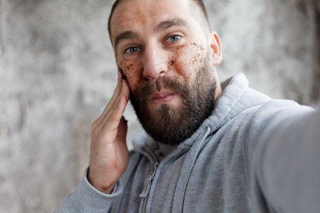 Sport, health, people, emotions, lifestyle concept - handsome man with three different face masks chocolate, cream and clay masks. photo of man with perfect skin. grooming himself