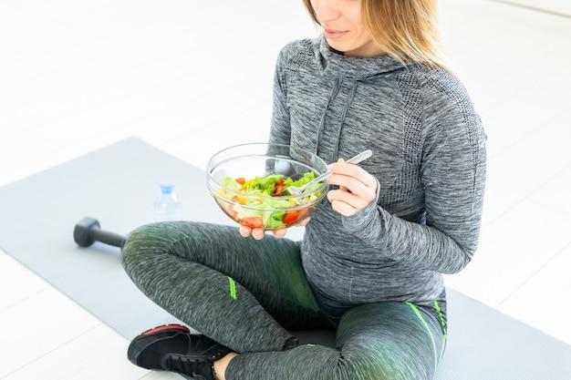 スポーツ、健康的なライフスタイルと人々の概念-床に座っているサラダとダンベルを持つ若い女性。