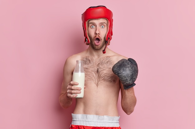 Sport and healthy lifestyle concept. shocked man in boxing glove and hat has training in gym stares impressed keeps to protein diet drinks milk as source of calcium.