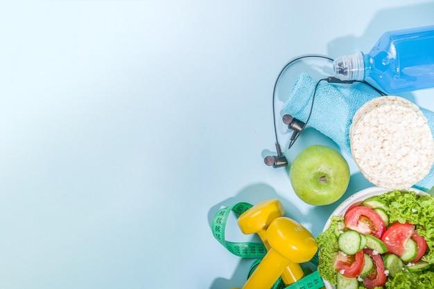 스포츠 건강한 라이프 스타일, 다이어트 개념입니다. 측정 테이프, 컬러 덤벨, 샐러드, 시리얼 바삭한 빵, 파란색 배경 복사 공간에 스포츠 물병을 사용하여 체중 감량 피트니스 배경을 슬리밍