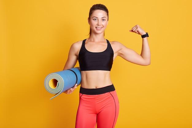 スポーツ、健康的なライフスタイル、ジム、良好な身体状態、フィットネスの概念。若いスポーティな笑顔ブルネットの女性の肖像画を閉じる