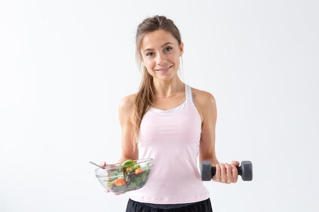 스포츠, 건강한 생활 방식, 사람들의 개념 - 샐러드와 아령을 가진 젊은 갈색 머리 여성. 그녀는 웃고 건강한 생활 방식을 즐기고 있습니다.
