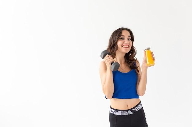 スポーツ、健康的なライフスタイル、人々の概念-若い女性は、コピースペースと白い背景にジュースのボトルとダンベルを保持します。