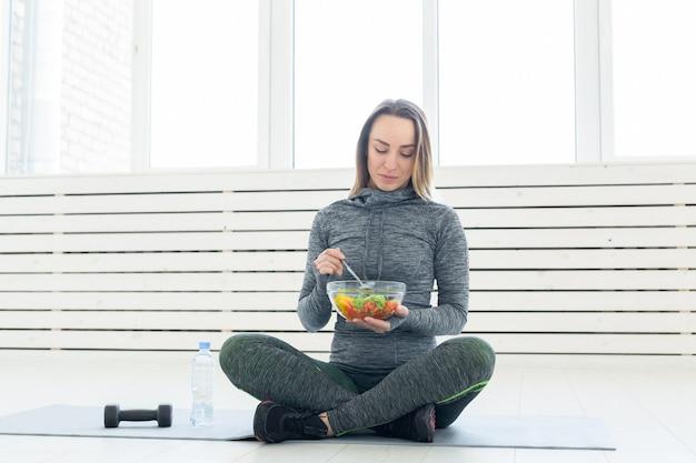 スポーツ、健康、人々の概念-フィットネストレーニング後にサラダとダンベルを保持している女の子
