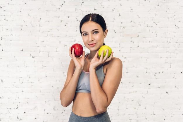 白い壁に分離された赤いリンゴを保持しているスポーツ健康な女性