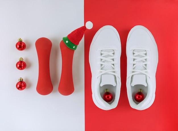スポーツホリデーフラットレイ。白と赤の床にかわいい帽子をかぶったクリスマスボール、トレーナー、ダンベル。