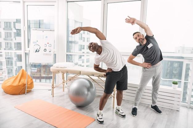 スポーツは人生です。リハビリ療法をしながら運動している快適な素敵な男性