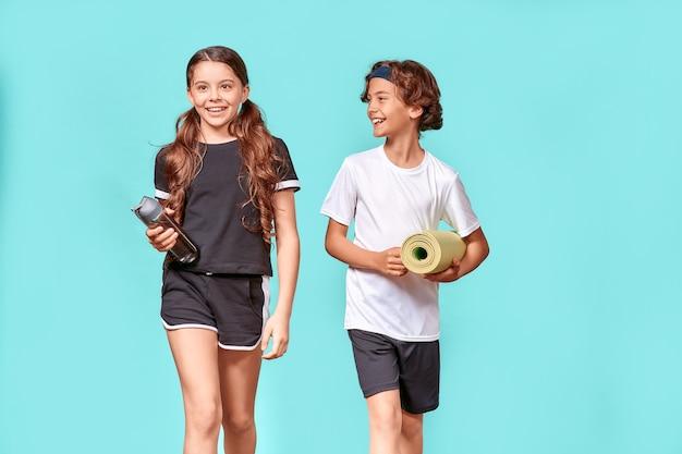 스포츠는 요가 매트와 카메라를 보고 있는 물 한 병을 가진 두 십대 소년과 소녀의 삶입니다.
