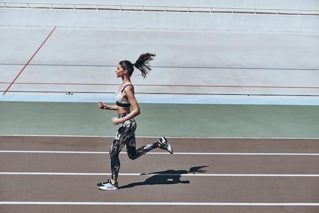 Спорт - это образ его жизни. полная длина вид сверху молодой женщины в спортивной одежде бег трусцой