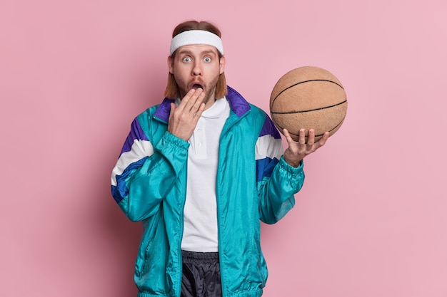 Sport leisure lifestyle concept. stupefied unshaven sportsman basketball player holds ball dressed in sports clothes going to play game with friends being active