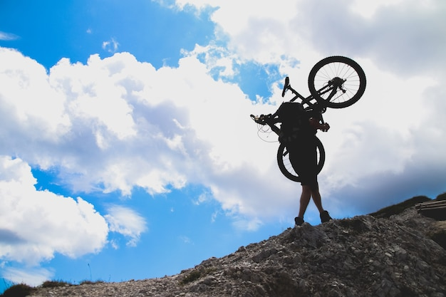 Sport man in action lifting bike on his shoulder on rock mountain with blue sky background.