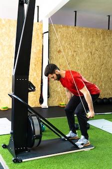 ジムのスキーヤーのシミュレーションマシンで運動をしているスポーツ男