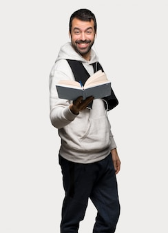 Sport man holding a book and giving it to someone over isolated grey background