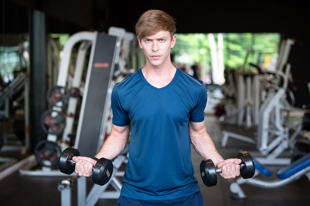 Sport man holding dumbbell during an exercise class in a gym