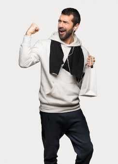 Sport man holding a lot of shopping bags in victory position over isolated grey background