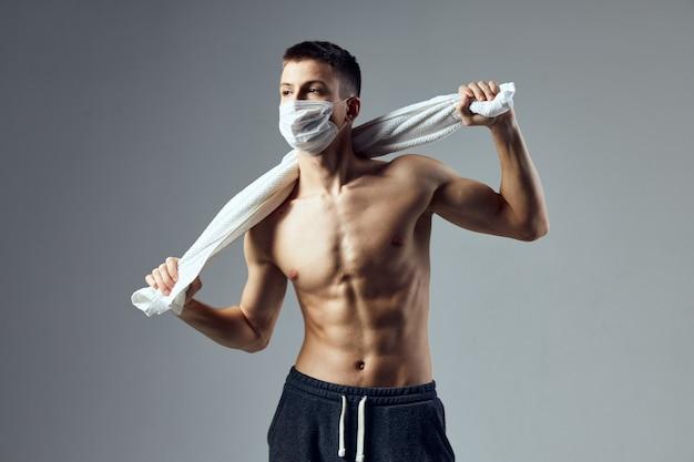 頭の後ろにタオルを持っているスポーツ男膨らんだプレス医療マスク隔離された壁