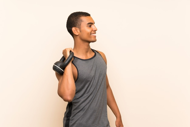 Sport man over isolated background with kettlebell