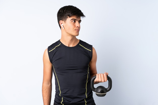 Sport man over isolated blue making weightlifting with kettlebell