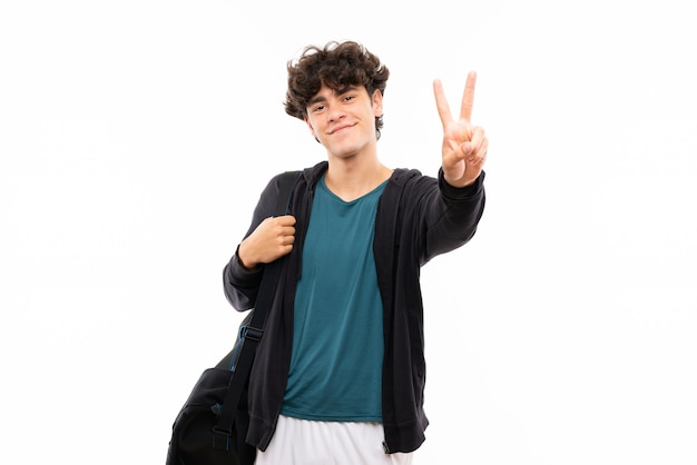 Sport man over isolated white  smiling and showing victory sign