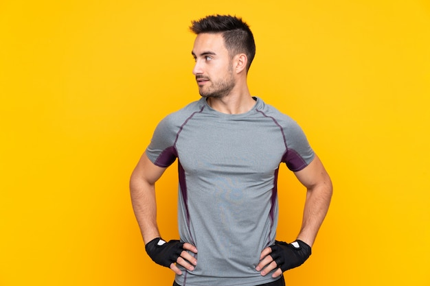 Sport man over isolated yellow wall posing with arms at hip and looking side