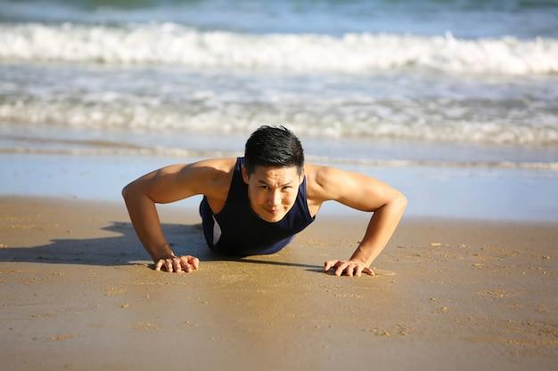 Спортивный человек делает упражнения на пляже утром