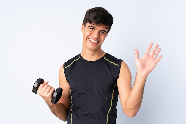 Sport man making weightlifting over blue wall saluting with hand with happy expression