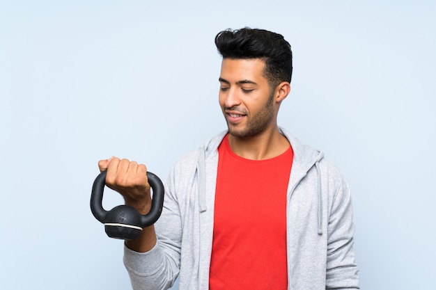 Sport man making weightlifting with kettlebell over isolated blue wall