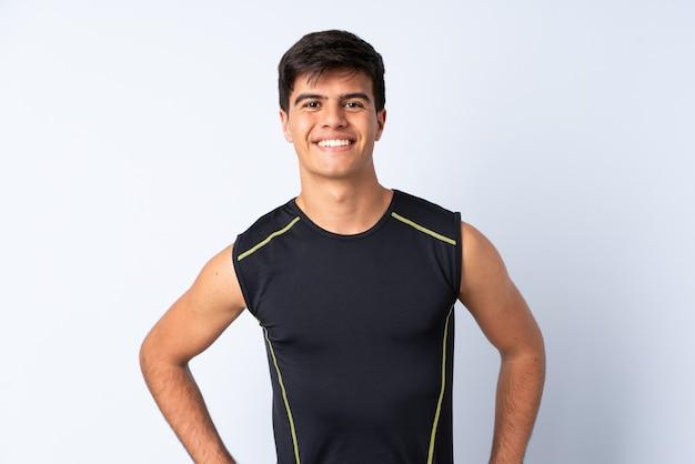 Спортивный человек над синим позирует с руки на бедра и улыбается