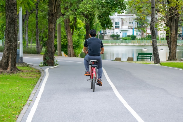 Sport man riding bicycle on road in the park.