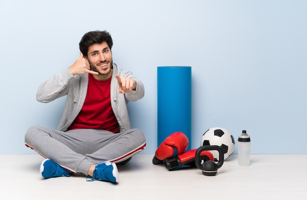 Sport man sitting on the floor making phone gesture and pointing front