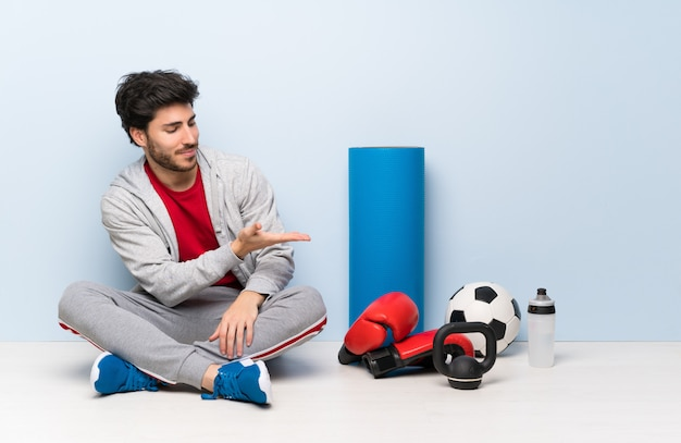 Sport man sitting on the floor presenting an idea while looking smiling towards