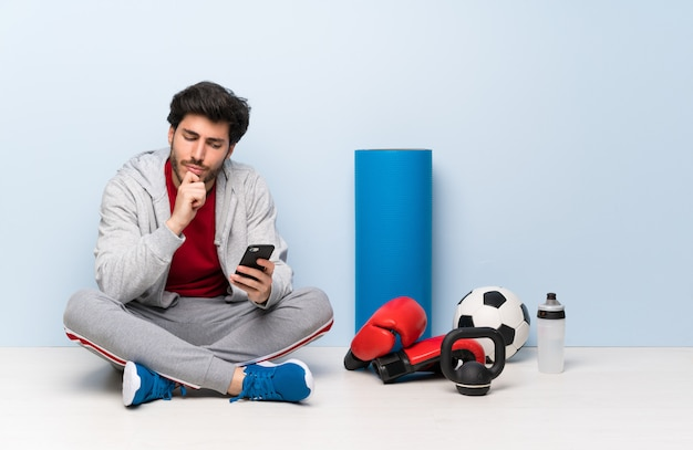 Sport man sitting on the floor thinking and sending a message