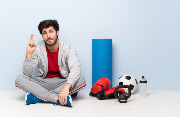 Sport man sitting on the floor with fingers crossing and wishing the best