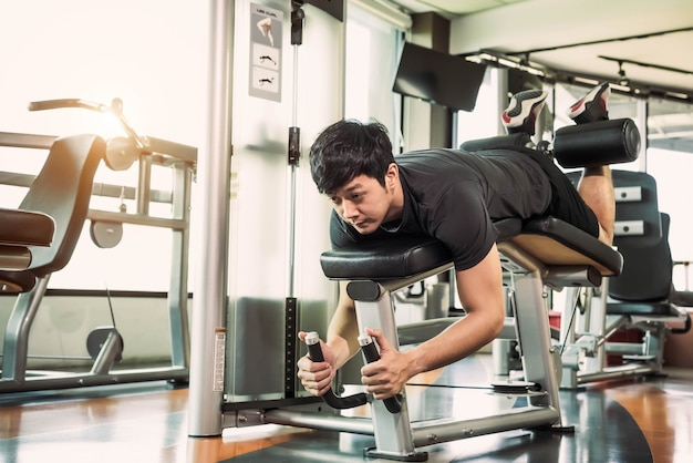 Sport man stretching and lifting weight by two legs when facing down for stretching muscle at fitness gym