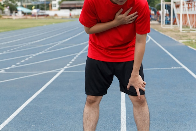 Sport man suffering from chest pain heart attack after running.