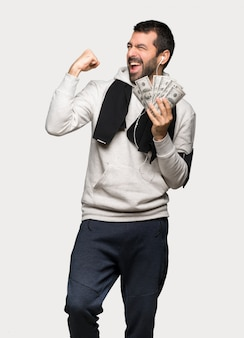 Sport man taking a lot of money over isolated grey background