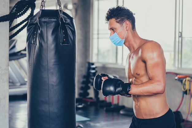 Sport man wear face mask for boxing at fitness gym. social distancing and wellness. fit and firm for healthy. mind-body improvements. new normal and life after covid-19.