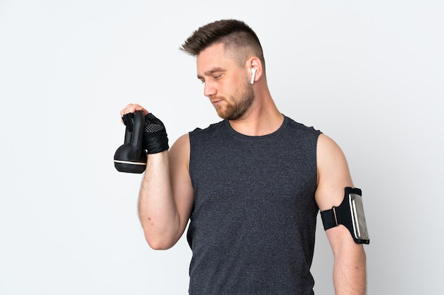 Sport man on white wall making weightlifting with kettlebell