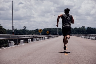 路上でランナーを持つスポーツ男が運動を実行していること