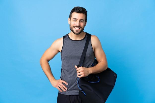 Спортивный мужчина со спортивной сумкой позирует с руками на бедрах и улыбается