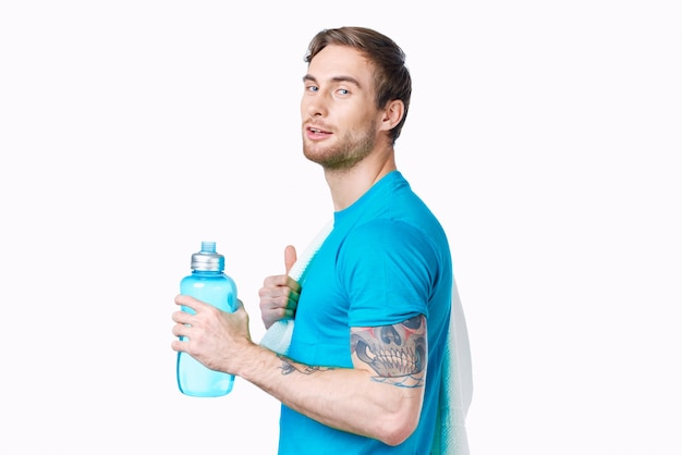 Sport man with tattoo on his arm workout water bottle cropped view light background