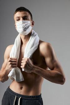 Спортивный человек с полотенцем на плечах надувает медицинскую маску туловища
