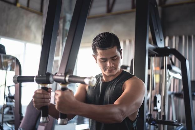 ジム設備スポーツクラブでウェイトトレーニングをしているスポーツマン