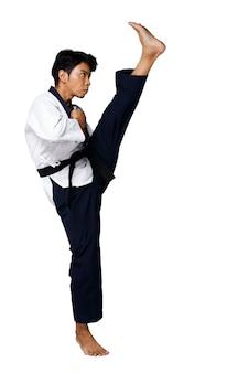 Мастер спорта по таэквондо практикует позы каратэ. инструктор носит традиционную униформу и показывает выступление poomsae kick на белом фоне, изолированном во всю длину