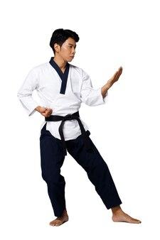 Мастер спорта по таэквондо практикует позы каратэ. инструктор носит традиционную униформу и показывает представление «пумсаэ пунш» на белом фоне, изолированном во всю длину
